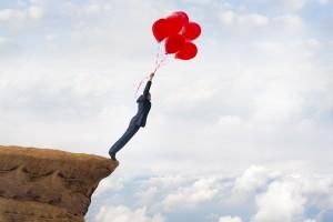 風船で空を飛ぼうとしている男性